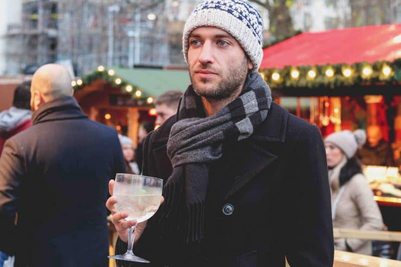 man holding drink winter christmas market